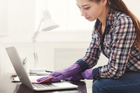 Woman cleaning laptop keyboard copy space