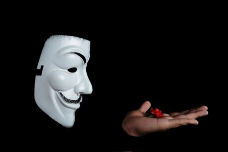 anonymous face mask looks at flower in hand